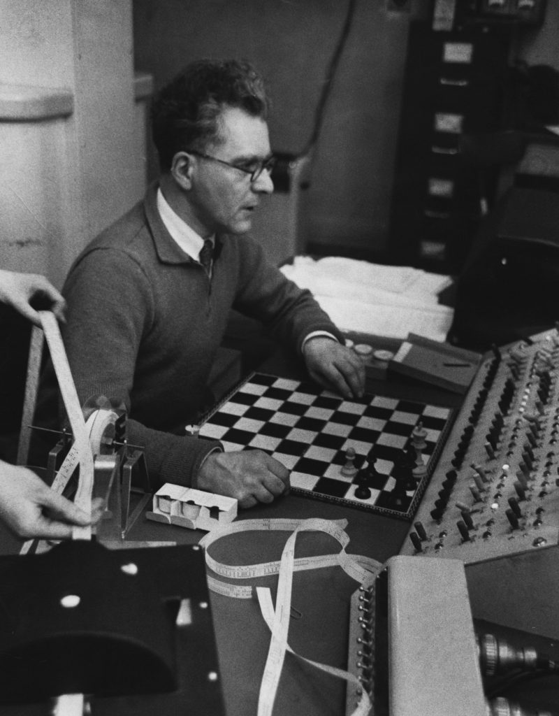 1955, Moston, Manchester, England, UK --- Doctor Prinz, of the Manchester firm Ferranti, sets one of its computers a chess problem. The computer, which is used at Manchester University, takes 15 minutes to respond to the problem but achieves checkmate in two moves. --- Image by © Hulton-Deutsch Collection/CORBIS